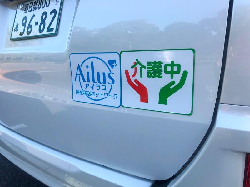 車両のリアに貼った福祉移送ネットワークアイラスのステッカーと介護中ステッカー