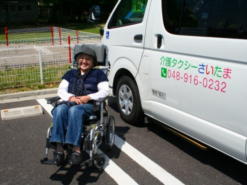 車両の前で車いすに乗った笑顔のお客様