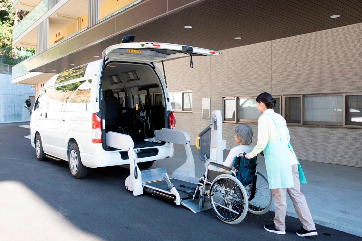 リフトに車いす利用者を乗せるヘルパー